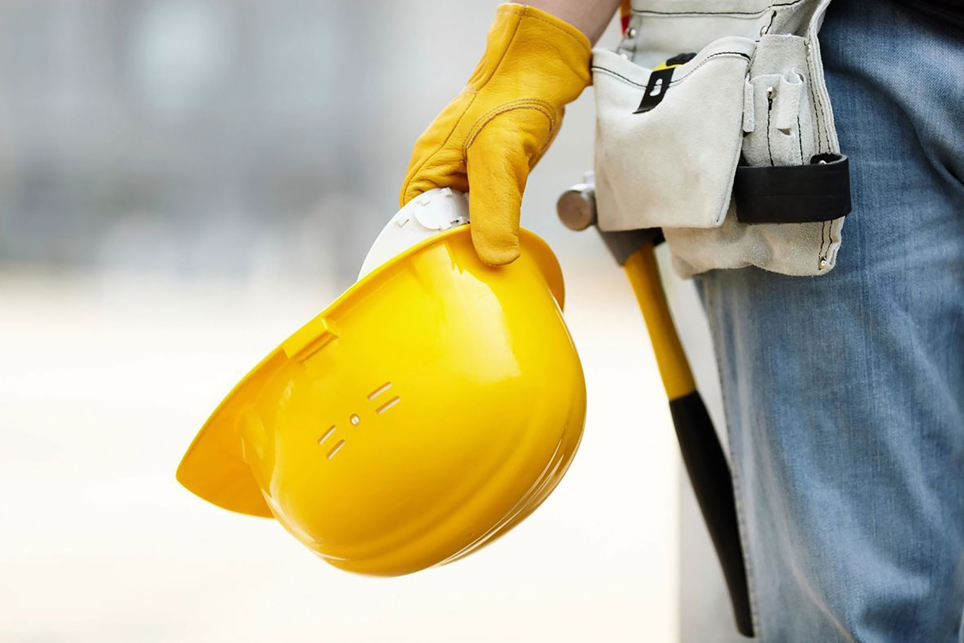 construction worker holding yellow safety hard hat